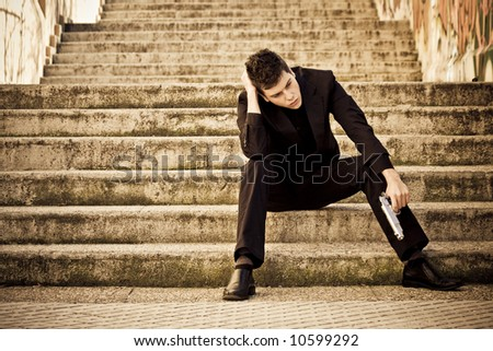 Young armed man waiting on the steps - stock photo