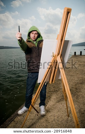 Young artist drawing outdoors in stormy weather - stock photo
