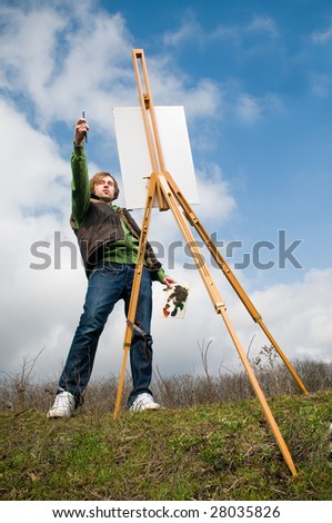Young artist drawing outdoors over blue sky background - stock photo