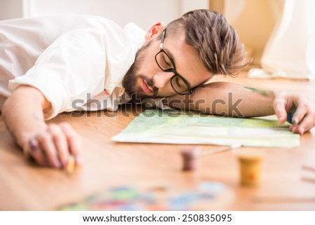 Young artist fell asleep while drawing his pictures. - stock photo