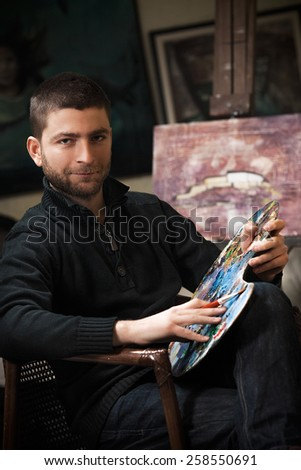 Young artist in his studio working on an oil painting. - stock photo