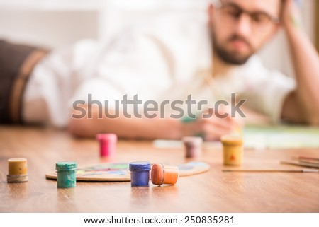 Young artist is painting on canvas is lying on studio floor. Close-up. - stock photo