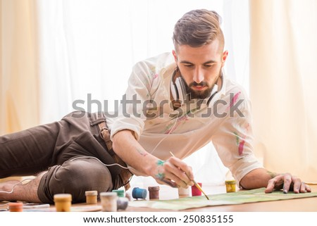 Young artist is painting on canvas is lying on studio floor while listening a music. - stock photo