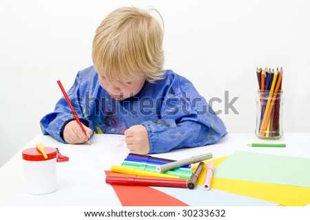 Young artist making a drawing, using pencils, felt pens, glue, scissors and paper