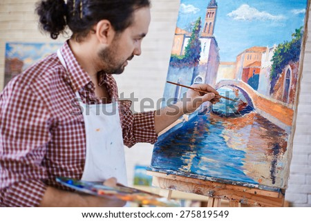 Young artist painting Italian landmark in studio - stock photo
