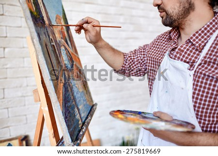 Young artist painting with oilpaints on canvas - stock photo