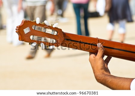 Young artist plays guitar outside in the park full of people - stock photo