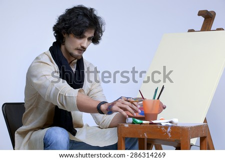 Young artist sitting near easel against colored background - stock photo