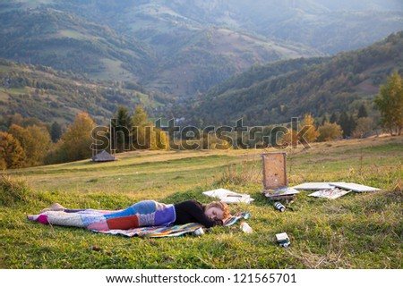 Young artist sleeping in a mountain meadow - stock photo