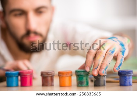 Young artist with paints. Close-up. Focus on paints. - stock photo