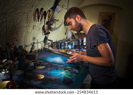 Young artist working in his studio creating spray paint art. - stock photo