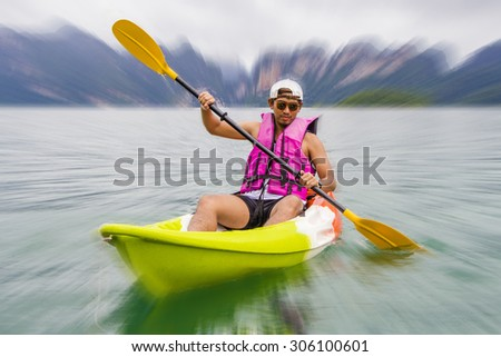 Young Asia man paddling in Chiewlarn dam in Surat Thani, Thailand With Zoom motion Blur Effect