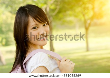 Young Asian adult student standing on campus lawn, with backpack and smiling. - stock photo