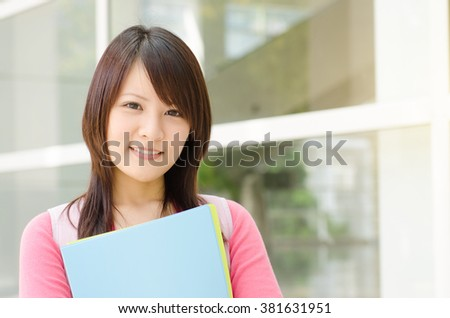 Young Asian adult student standing outside campus building, holding file folder and smiling. - stock photo