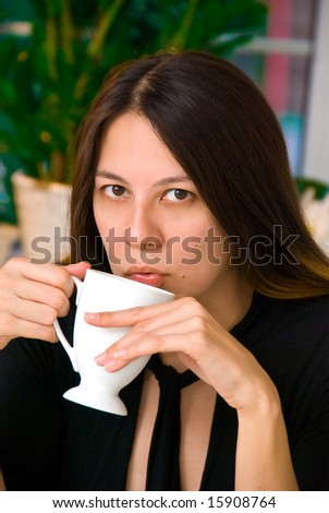 Young Asian American woman blowing into a hot cup of coffee - stock photo