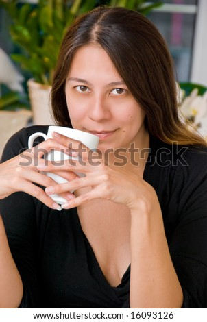 Young Asian American woman having a cup of coffee - stock photo