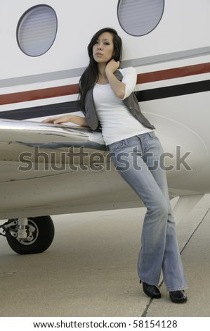 Young Asian-American woman in blue jeans leans against wing of passenger airplane on tarmac