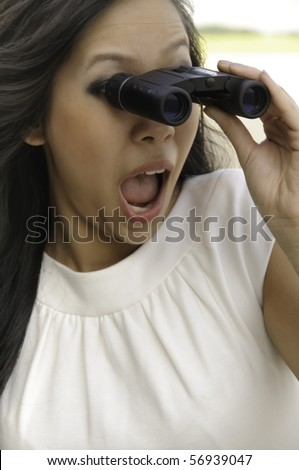 Young Asian-American woman looks surprised as she gazes through binoculars