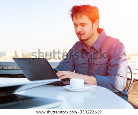 Young Asian Bearded Businessman Working on Computer at White Office Desk with Urban Landscape on Background Casual Clothing Shining Sun Back-light