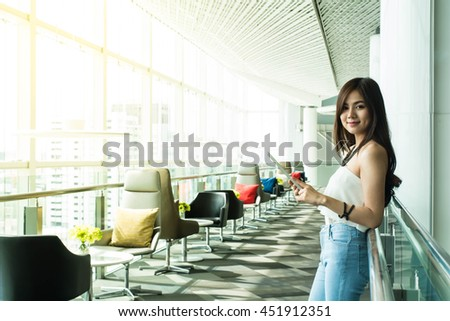 Young Asian beautiful businesswoman in casual clothes smile and standing while holding tablet at office lounge with sun flare  - stock photo