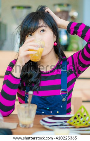 Young asian beautiful woman drinking fresh orange juice in cafe - stock photo
