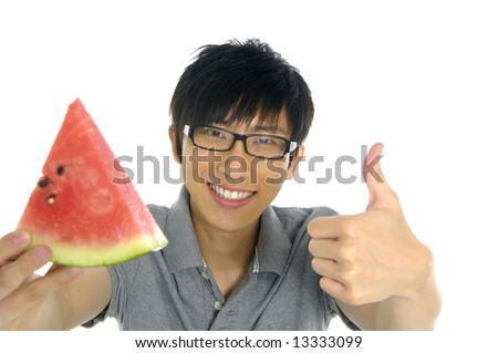 young Asian boy eating fruit - stock photo