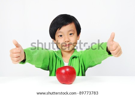 Young Asian boy gives thumbs up for healthy food ( red apple) - stock photo