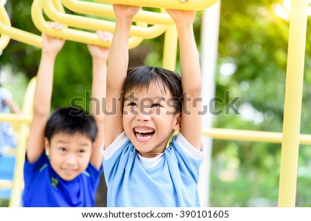 Young asian boy hang the yellow bar by his hand to exercise at out door playground under the big tree. - stock photo