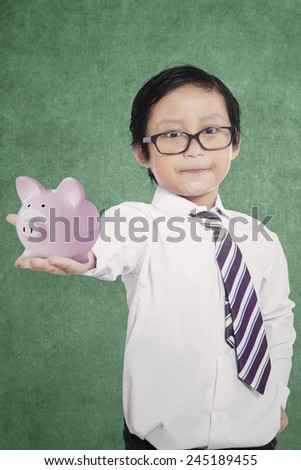 Young asian boy holding a piggy bank in the classroom with blackboard background - stock photo