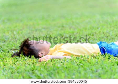Young Asian boy in yellow shirt lay down on green grass in the park during summer time. - stock photo