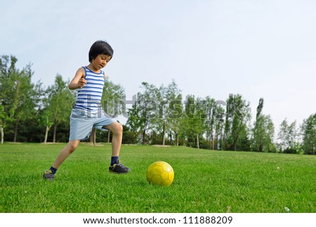 Young Asian boy kicking a yellow ball - stock photo
