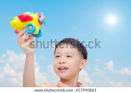 Young asian boy playing with plastic plane over sky background - stock photo