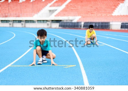 Young Asian boy prepare to start running with another boy on blue track in the stadium during day time to practice himself. - stock photo