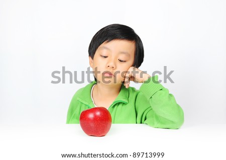 Young Asian boy reluctant to eat healthy food ( red apple ) - stock photo