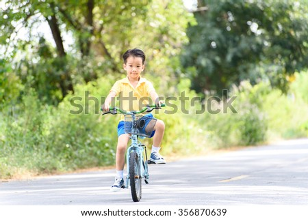 Young Asian boy ride a blue bicycle on the old road beside the tree and grass in summer time with warm sunlight.