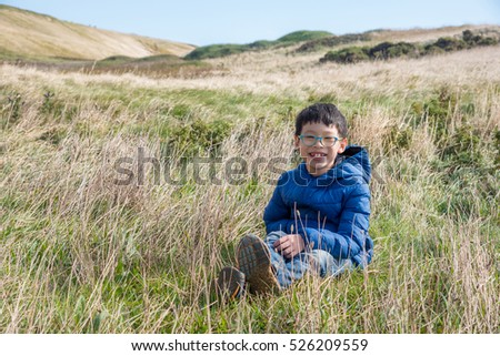 Young asian boy sitting in grass field