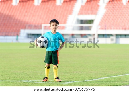 Young Asian boy stand in the grass football field in the stadium during summer. - stock photo