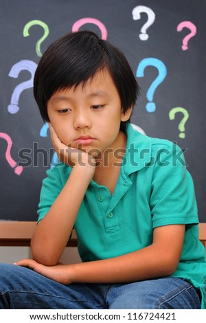 Young Asian boy thinking - stock photo