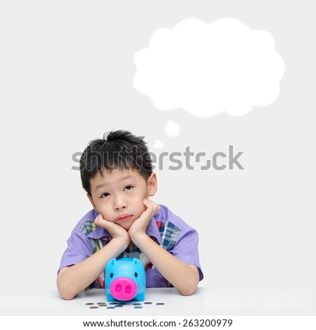 Young Asian boy thinking what to buy with his savings money - stock photo