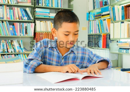 young asian  boy with book in Library. - stock photo