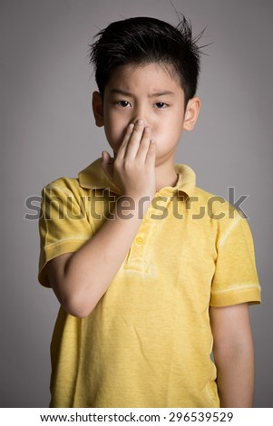 Young asian boy with both hands closing mouth on gray background - stock photo