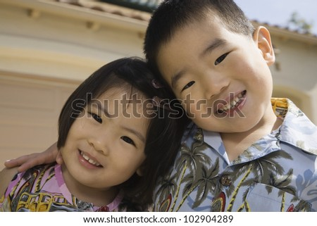 Young Asian brother and sister hugging and smiling outdoors