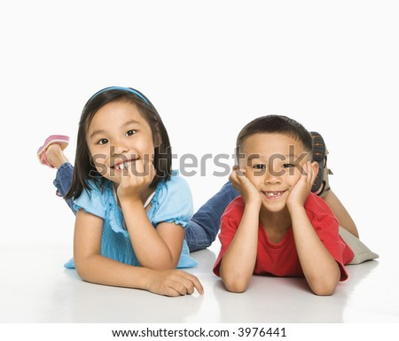 Young Asian brother and sister lying on floor with head on hands.