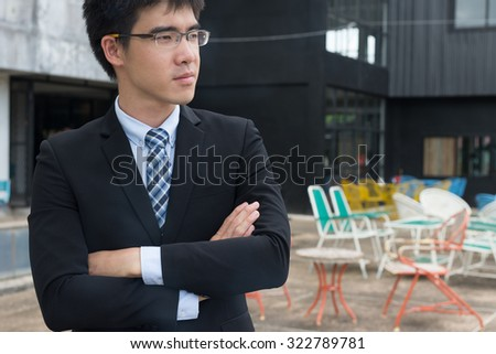 young asian business man cross himself's arm looking forward for conceptual use gesture of looking forward to the great future  - stock photo