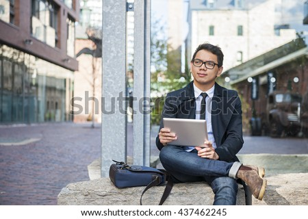 Young  asian business man holding a digital tablet sitting outside on city street looking thoughtful and concerned - stock photo