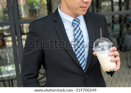 young asian business man holding his cold coffee cup for conceptual use - stock photo