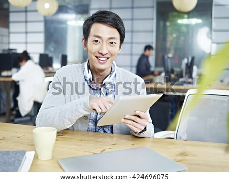 young asian business man sitting at desk in office holding tablet computer looking at camera smiling. - stock photo