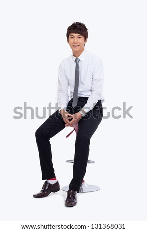 Young Asian business man sitting on the chair isolated on white background.
