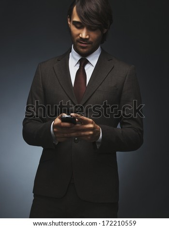 Young asian business man text messaging on his smartphone on black background. Attractive male model in suit holding smart phone texting. - stock photo