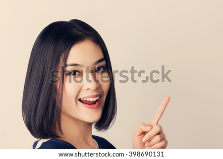 Young Asian business woman in white shirt and pointing index on free space. vintage tone filter. - stock photo